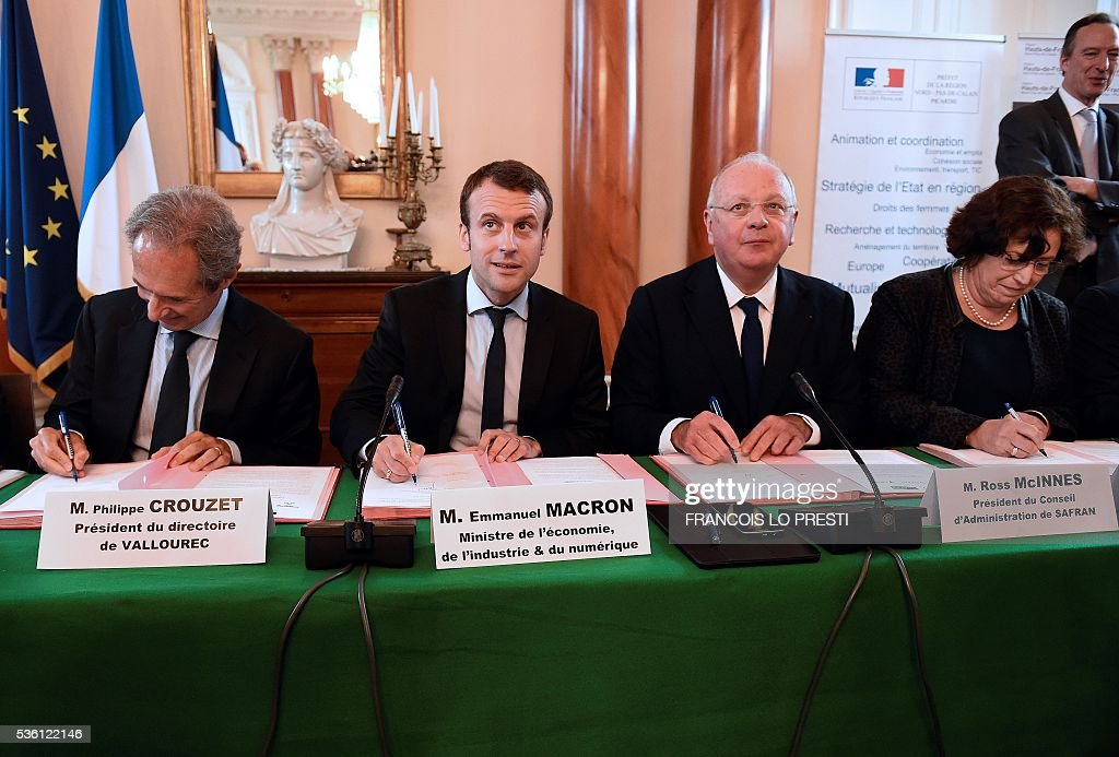 French Economy Minister Emmanuel Macron (2ndL), French steel group Vallourec chief executive Philippe Crouzet (L), French aircraft engine maker Safran Group chairman of the board Ross McInnes (2ndR) and Air France industries general director Anne Brachet sign an agreement on May 31, 2016 at the Valenciennes' sous-prefecture after a meeting on reindustrialisation in the North of France. / AFP / FRANCOIS