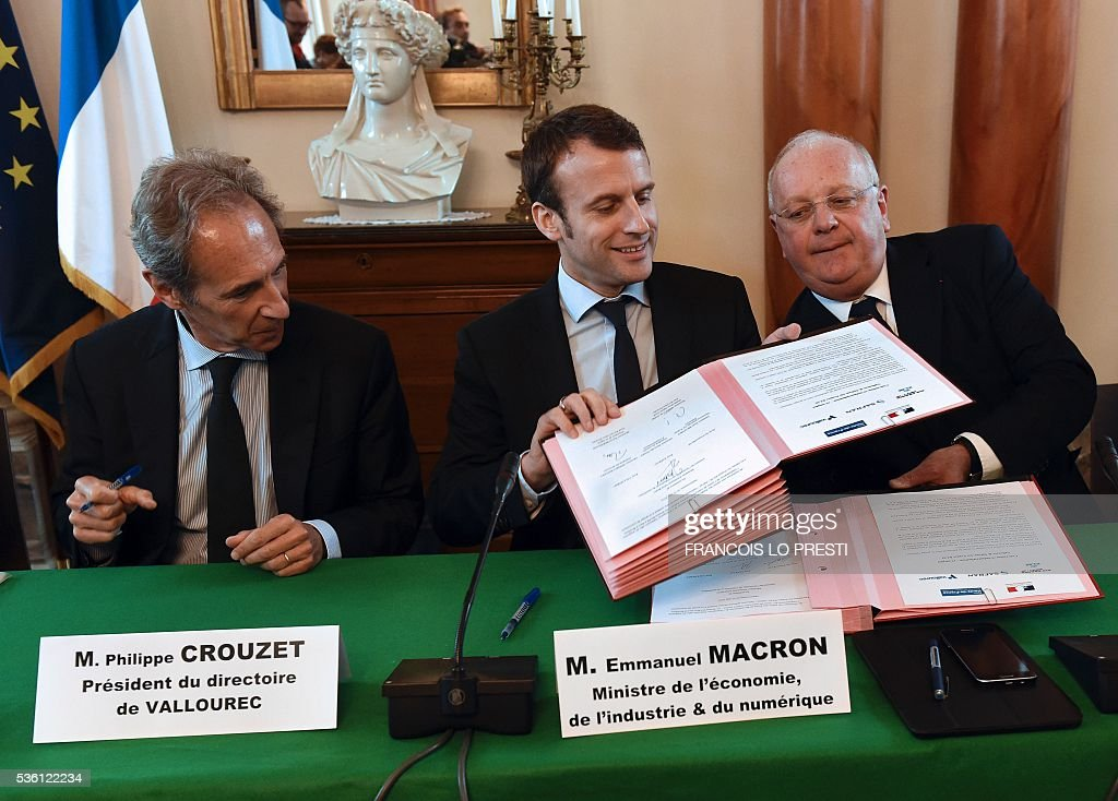 French Economy Minister Emmanuel Macron (C), French steel group Vallourec chief executive Philippe Crouzet (L) and French aircraft engine maker Safran Group chairman of the board Ross McInnes exchange documents as they sign an agreement on May 31, 2016 at the Valenciennes' sous-prefecture after a meeting on reindustrialisation in the North of France. / AFP / FRANCOIS
