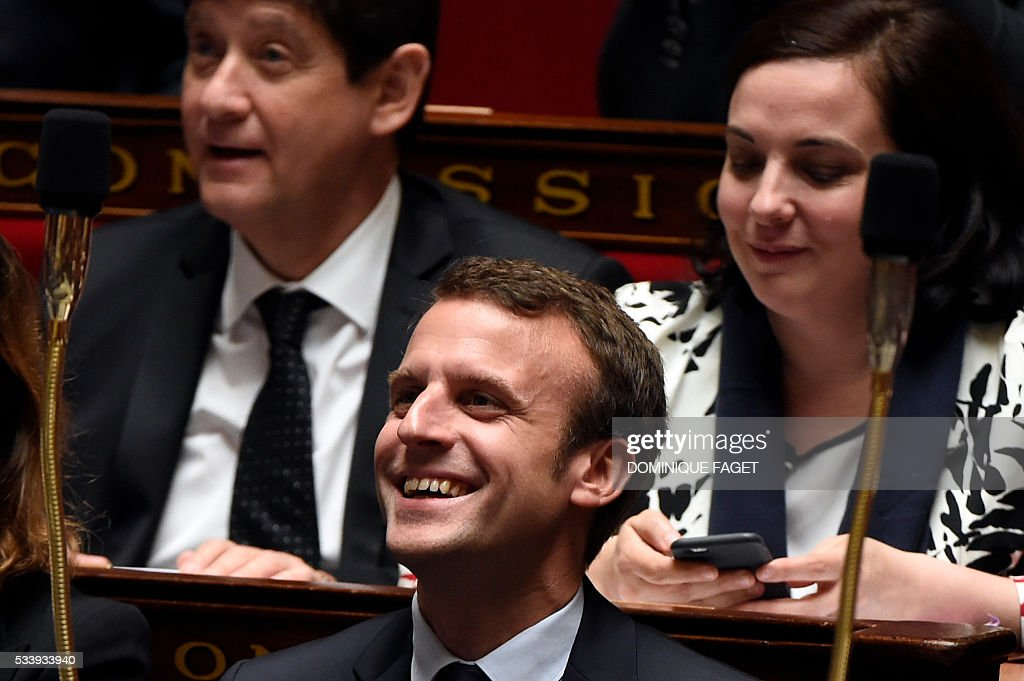 French Economy minister Emmanuel Macron laughs during a session of Questions to the Government, on May 24, 2016 at the National Assembly in Paris.