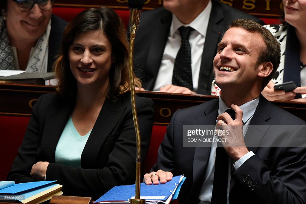 French Economy minister Emmanuel Macron (R) laughs during a session of Questions to the Government, on May 24, 2016 at the National Assembly in Paris.