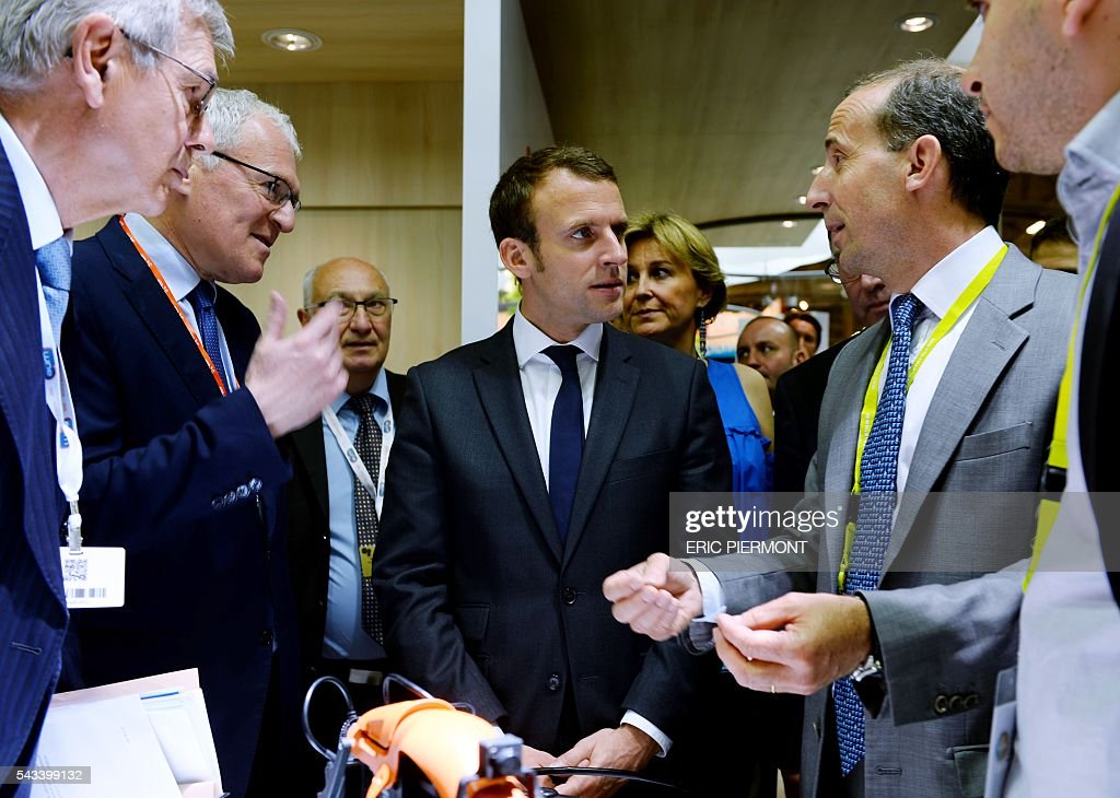 French Economy Minister Emmanuel Macron (2nd R) listens to explanations of French nuclear giant Areva's Chief Executive Officer, Philippe Knoche (R) flanked by Areva Chairman of the Board of Directors Philippe Varin (L) and France's state-run power firm EDF Chief Executive Jean-Bernard Levy (2nd L) while visiting the Areva stand at the World Nuclear Exhibition in Le Bourget, near Paris on June 28, 2016. / AFP / ERIC