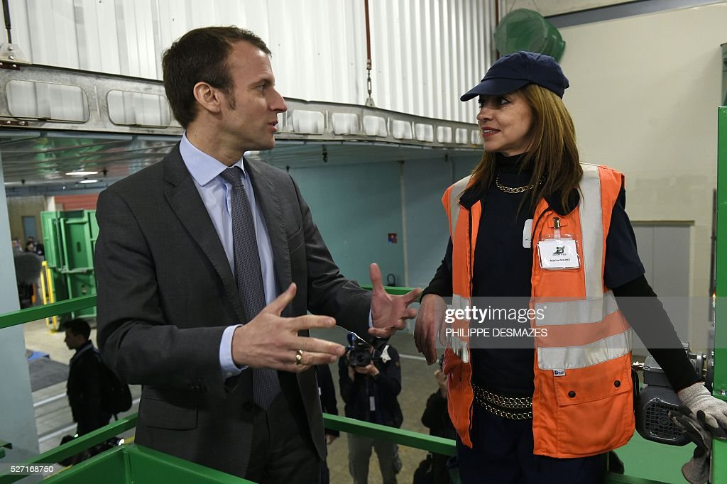French Economy minister Emmanuel Macron (L) meets with a worker during a visit within the inauguration of ID'EES group's new factory IDEM, that produces cellulose wadding from cardboard, on May 2, 2016, in Fragnes central-eastern France. ID'EES group is one of the French leaders of people's integration through the economic sector. / AFP / PHILIPPE
