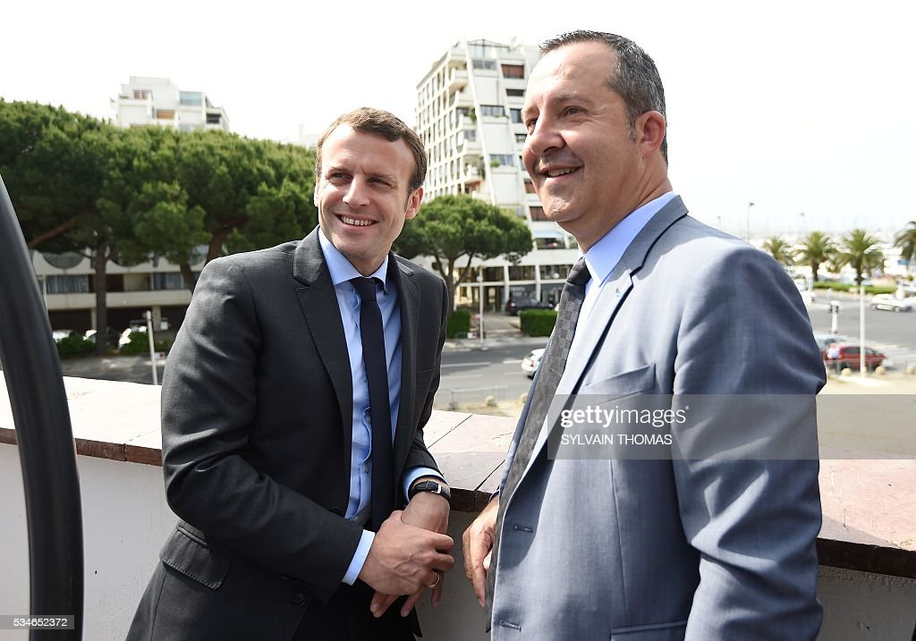 French Economy minister Emmanuel Macron (L) poses with Stephane Rossignol (R), La Grande-Motte Mayor, during a meeting of the 'Association des petites villes de France' (Association of Small Towns in France) on May 27, 2016 in La Grande-Motte, southern France. / AFP / SYLVAIN