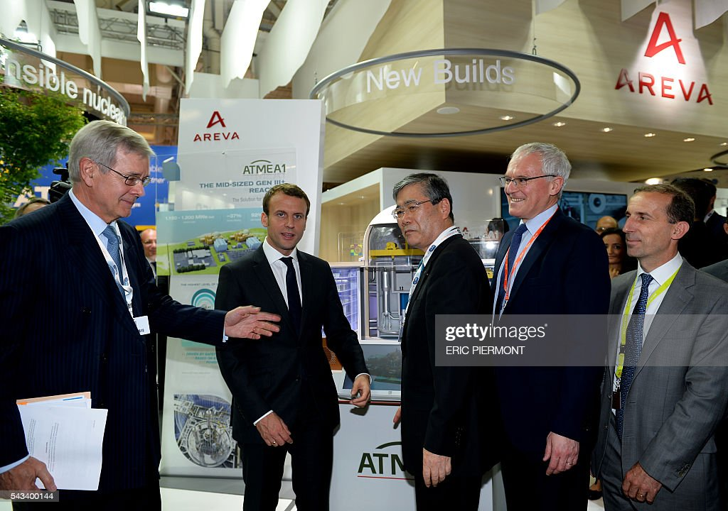 French Economy Minister Emmanuel Macron (2ndL) prepares to pose for a picture along with French nuclear giant Areva's Chairman of the Board of Directors Philippe Varin (L), Mitsubishi Heavy Industries (MHI) President and CEO Shunichi Miyanaga (3rd L), France's state-run power firm EDF Chief Executive Jean-Bernard Levy (2nd R) and Areva's Chief Executive Officer, Philippe Knoche (R) in front of an ATMEA reactor model While visiting the Areva stand at the World Nuclear Exhibition in Le Bourget, near Paris on June 28, 2016. ATMEA company is a joint venture between Areva and MIH. / AFP / ERIC