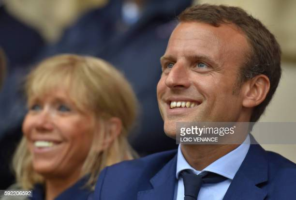 French Economy Minister Emmanuel Macron reacts next to his wife Brigitte Trogneux during a visit at the PuyduFou theme park on August 19 2016 in Les...