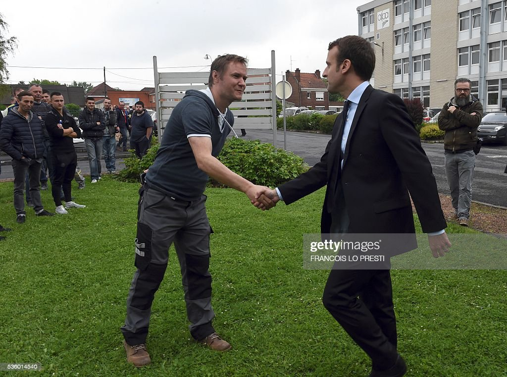 French Economy Minister Emmanuel Macron shakes hands as he visits the AFPA 'La Sentinelle' training centre on May 31, 2016 in Valenciennes, after a meeting on reindustrialisation in the North of France. / AFP / FRANCOIS
