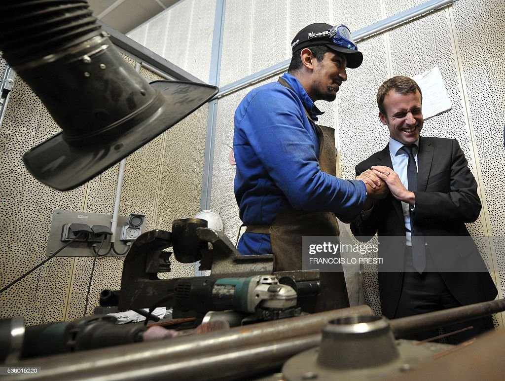 French Economy Minister Emmanuel Macron (R) shakes hands with a worker during a visit to the AFPA 'La Sentinelle' training centre on May 31, 2016 in Valenciennes, after a meeting on reindustrialisation in the North of France. / AFP / FRANCOIS