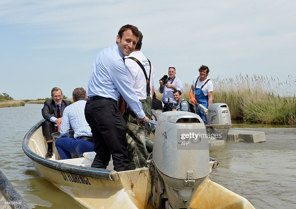 French Economy Minister Emmanuel Macron (C) smiles as he steers a motorboat on the lake of 'Etang de l'Or' on May 27, 2016. / AFP / SYLVAIN