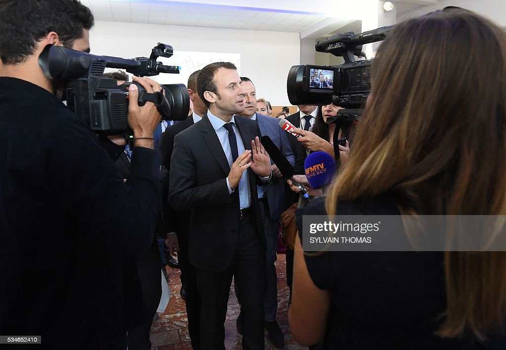 French Economy minister Emmanuel Macron (C) speaks to journalists after a meeting of the 'Association des petites villes de France' (Association of Small Towns in France) on May 27, 2016 in La Grande-Motte, southern France. / AFP / SYLVAIN