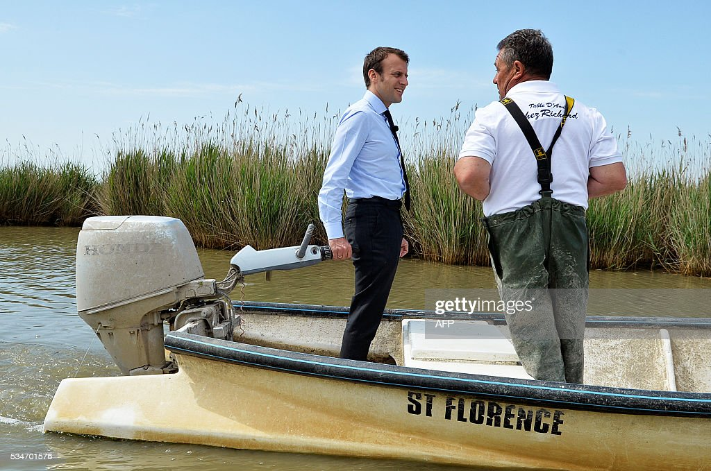 French Economy Minister Emmanuel Macron (L) speaks with a fisherman as he steers a motorboat on the lake of 'Etang de l'Or' on May 27, 2016. / AFP / SYLVAIN