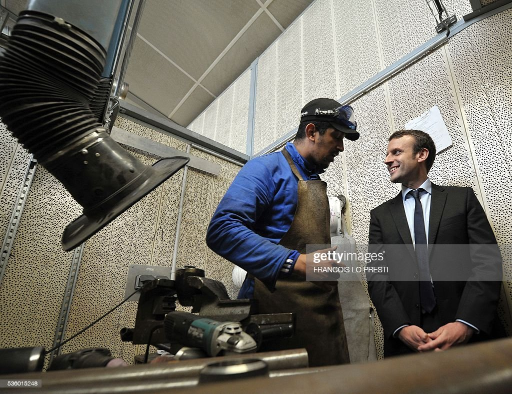 French Economy Minister Emmanuel Macron (R) speaks with a worker during a visit to the AFPA 'La Sentinelle' training centre on May 31, 2016 in Valenciennes, after a meeting on reindustrialisation in the North of France. / AFP / FRANCOIS