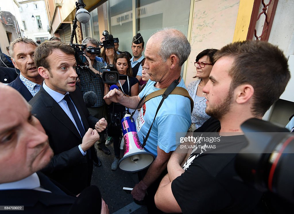 French Economy Minister Emmanuel Macron (L) speaks with protesters about the controversial government's labour reform, during a visit in Lunel on May 27, 2016. / AFP / SYLVAIN