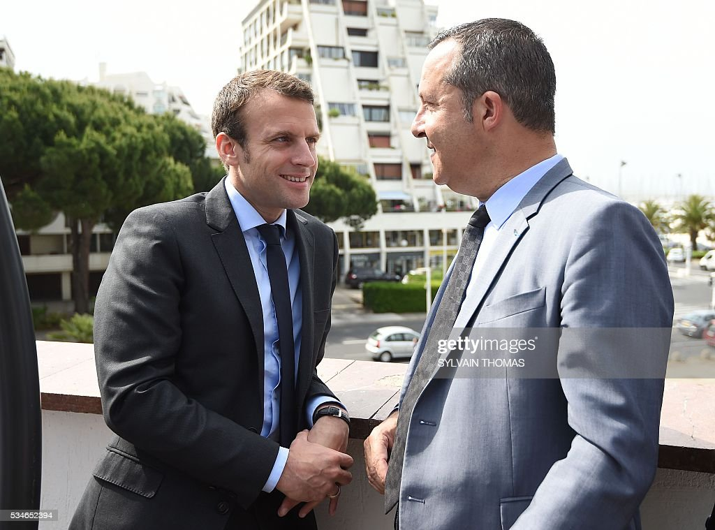 French Economy minister Emmanuel Macron (L) speaks with Stephane Rossignol (R), La Grande-Motte Mayor, during a meeting of the 'Association des petites villes de France' (Association of Small Towns in France) on May 27, 2016 in La Grande-Motte, southern France. / AFP / SYLVAIN