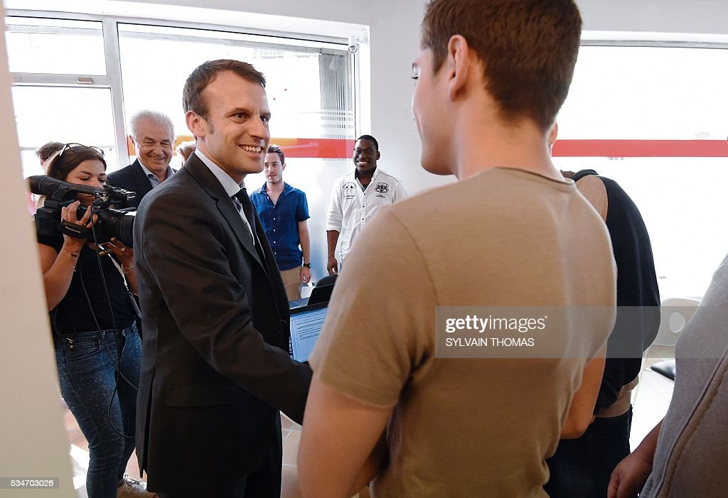 French Economy Minister Emmanuel Macron (L) speaks with young people during a visit to Be Web in Lunel on May 27, 2016. / AFP / SYLVAIN