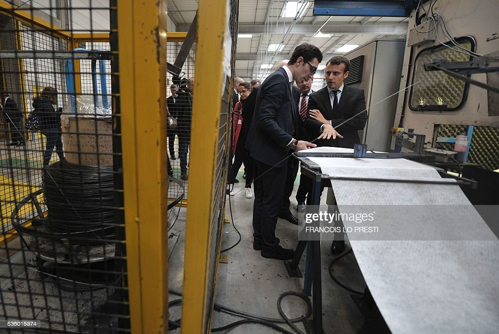 French Economy Minister Emmanuel Macron (R) visits the AFPA 'La Sentinelle' training centre on May 31, 2016 in Valenciennes, after a meeting on reindustrialisation in the North of France. / AFP / FRANCOIS