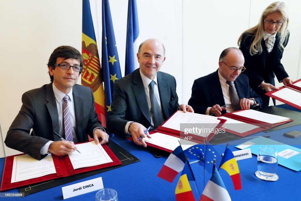 French Economy minister Pierre Moscovici (C) poses next to his Andorra's counterpart Jordi Cinca (L) as they sign a bilateral tax convention between the two countries, on April 2, 2013 at the ministry in Paris.
