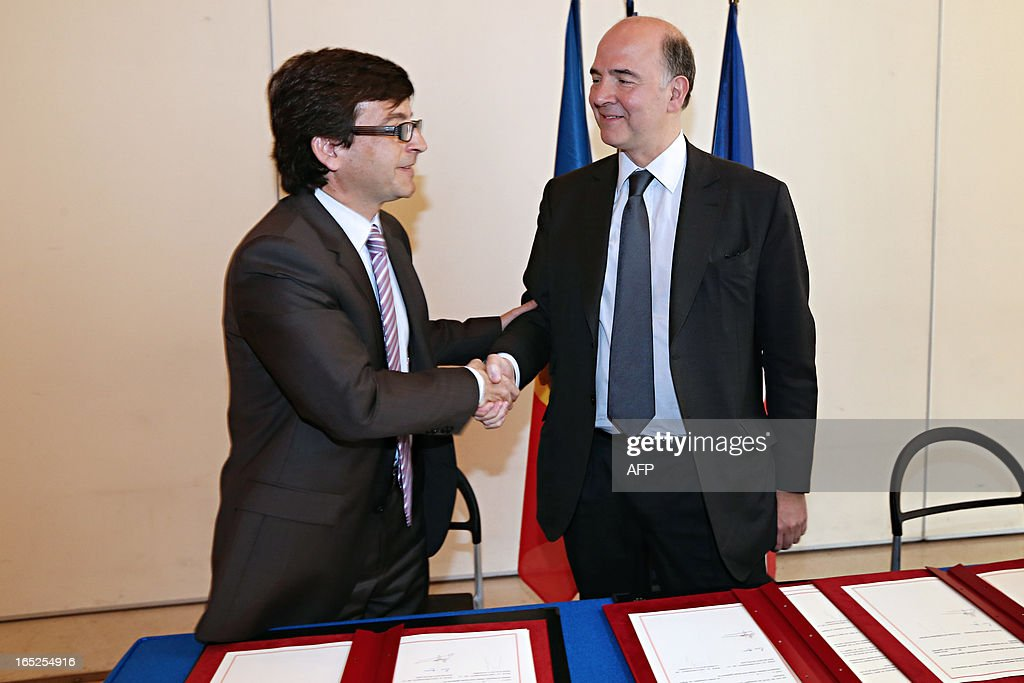 French Economy minister Pierre Moscovici (R) shakes hands with his Andorra's counterpart Jordi Cinca (L) prior to sign a bilateral tax convention between the two countries, on April 2, 2013 at the ministry in Paris. AFP PHOTO THOMAS SAMSON