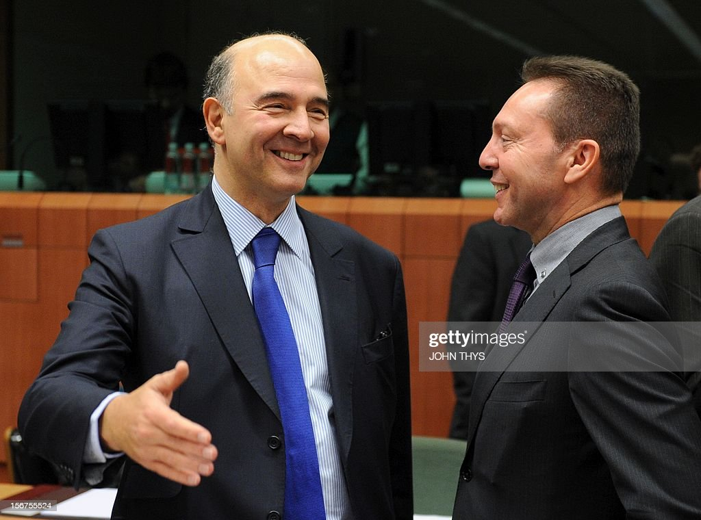 French Economy minister Pierre Moscovici (L) speaks with Greek Finance Minister Ioannis Stournaras (R) before an Eurozone finance ministers meeting to decide on a fresh rescue loan for debt-stricken Greece, on November 20, 2012 at EU headquarters in Brussels. Greece has 'delivered' on reform and a deal will likely be clinched to unblock funds to keep it from bankruptcy, the head of the Eurogroup insisted despite a split with the IMF over how to get the stricken country's economic recovery on track.