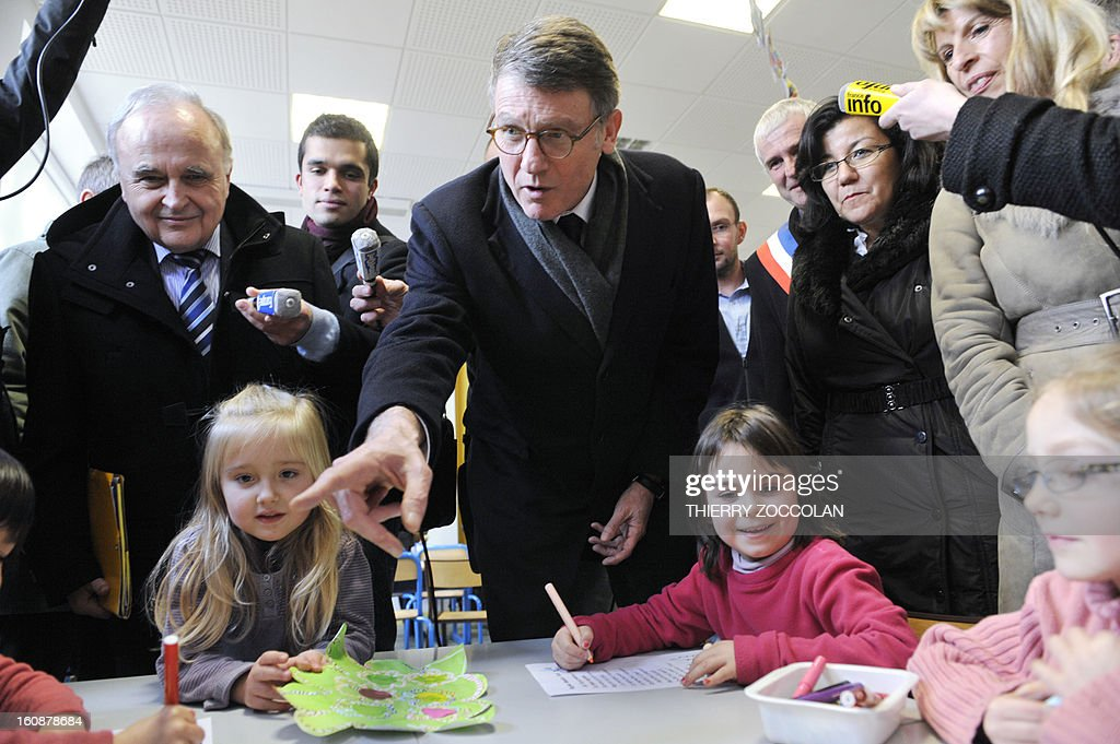 French Education Minister Vincent Peillon (C) points his finger to a pupil on February 7, 2013 during a visit to a primary school in Saint-Angel, central France. Peillon's visit is focused on a proposed reform to increase the class time of primary school students, planned for the 2013-2014 schoolyear, which foresees an increase of class time in primary schools to 4.5 days a week and would affect both students and teachers. AFP PHOTO THIERRY ZOCCOLAN
