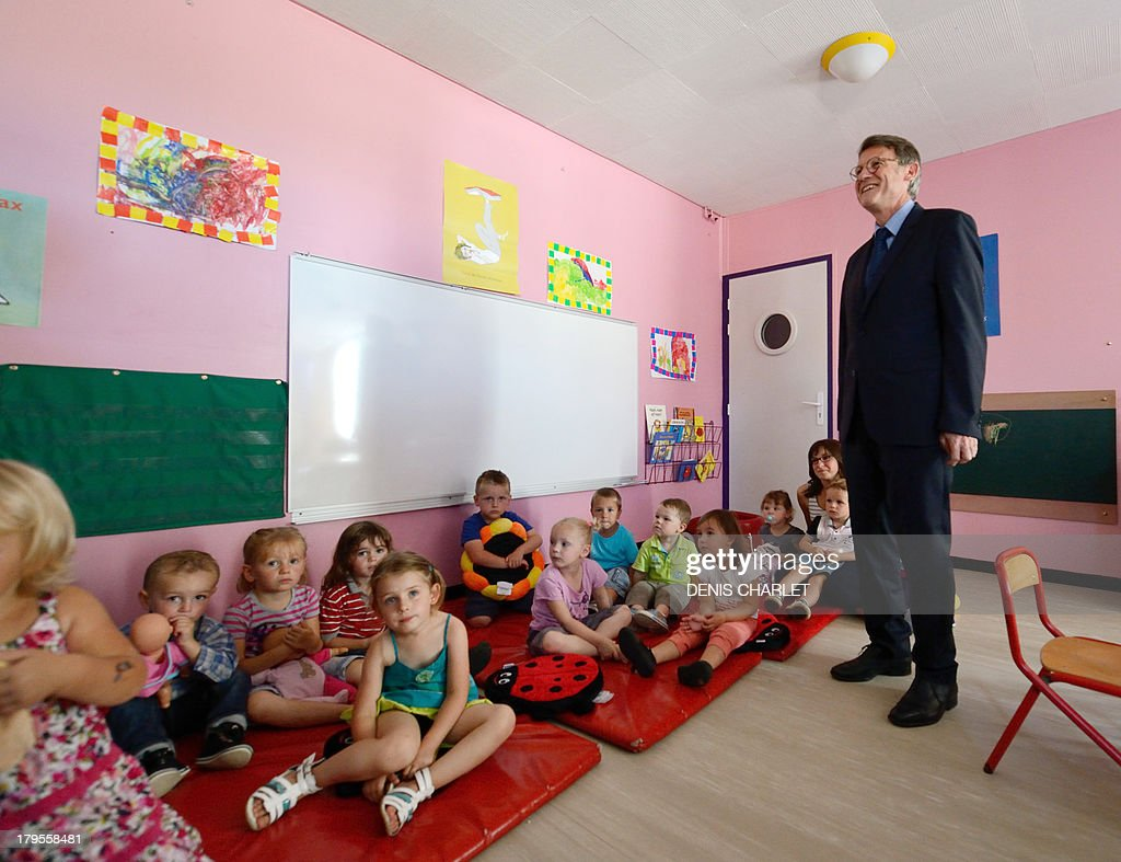 French Education Minister Vincent Peillon stands beside young pupils in a classroom at an infant school in Feuquières-en-Vimeu on September 5, 2013, during a visit focused on the government's reform of school timetables and on the schooling of children under three years old living in rural areas.