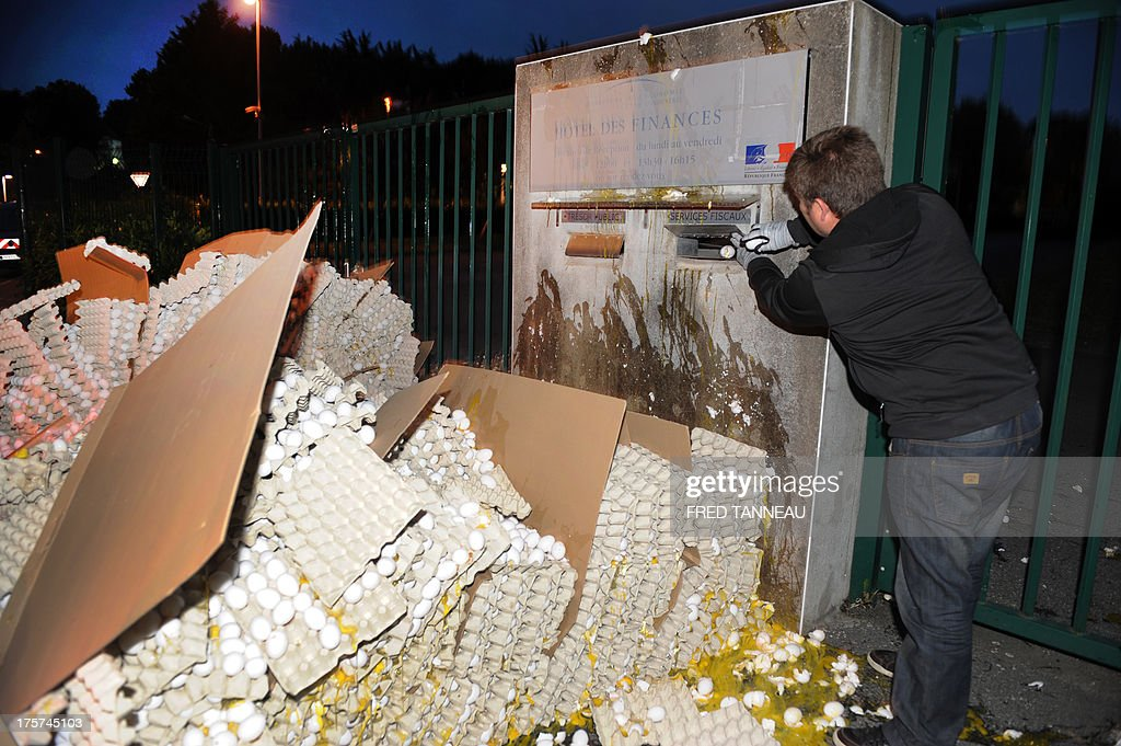 A French egg producer throws eggs in a mail box as he break eggs in front of the taxes and internal revenue service office in Carhaix-Plouguer, Brittany, western France, during a protest action, on August 7, 2013. In a context of European overproduction, a group of twenty egg producers in Brittany is protesting the low market value and pricing of eggs and called for up to 100 000 eggs (5 % of French daily production) to be broken everyday so as to raise the egg's market value. AFP PHOTO / FRED TANNEAU