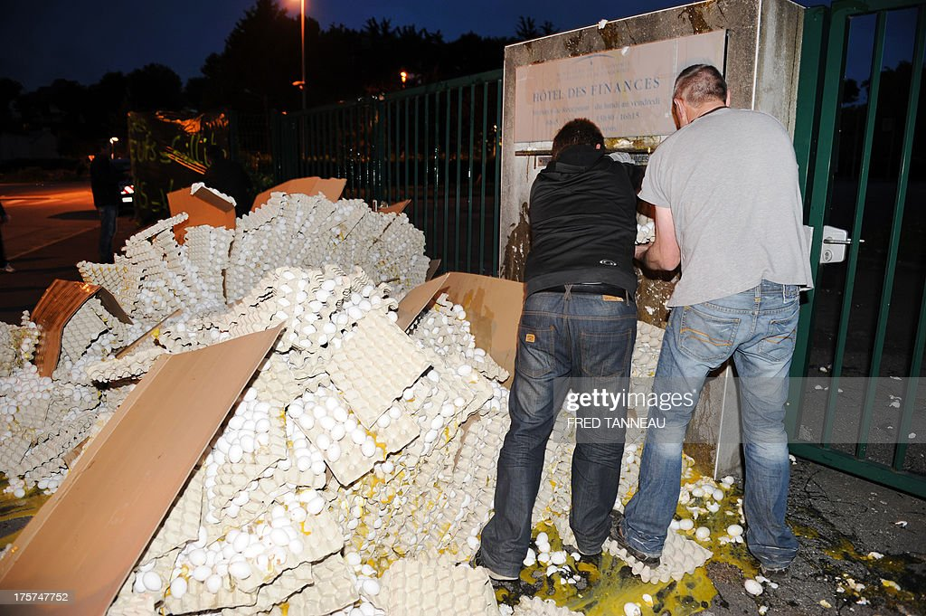 French egg producers break eggs in front of the taxes and internal revenue service office in Carhaix-Plouguer, Brittany, western France, during a protest action, on August 7, 2013. In a context of European overproduction, a group of twenty egg producers in Brittany is protesting the low market value and pricing of eggs and called for up to 100 000 eggs (5 % of French daily production) to be broken everyday so as to raise the egg's market value. AFP PHOTO / FRED TANNEAU