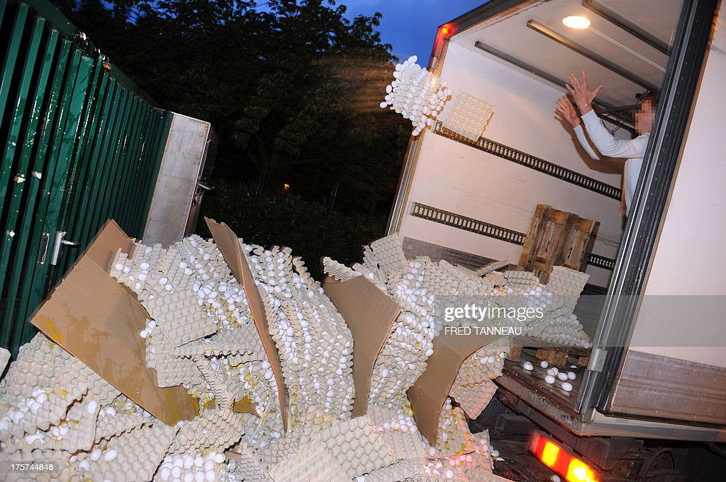French egg producers throw crates of eggs from the back of a truck onto the sidewalk in front of the taxes and internal revenue service office in Carhaix-Plouguer, Brittany, western France, during a protest action, on August 7, 2013. In a context of European overproduction, a group of twenty egg producers in Brittany is protesting the low market value and pricing of eggs and called for up to 100 000 eggs (5 % of French daily production) to be broken everyday so as to raise the egg's market value.