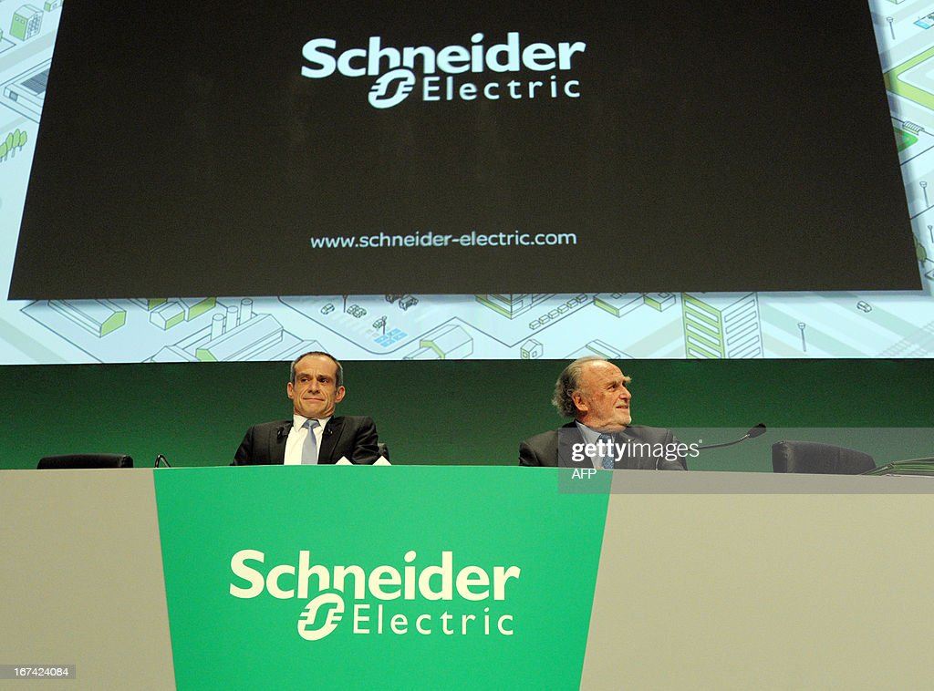 French electrical engineering giant Schneider Electric President and CEO Jean-Pascal Tricoire (L) and Chairman of the Supervisory Board Henri Lachmann arrive to attend the start of the group's shareholders meeting in Paris La Defense on April 25, 2013.