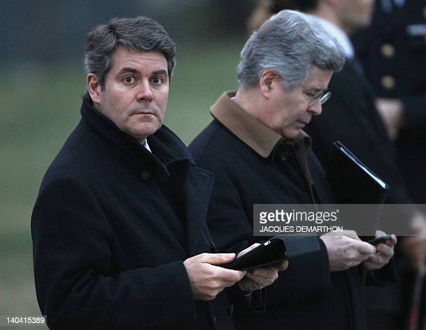 French Elysee presidential palace press advisor Franck Louvrier holds his ipad next to Elysee's diplomatic advisor JeanDavid Levitte as they wait for...