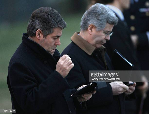French Elysee presidential palace press advisor Franck Louvrier looks a his ipad next to Elysee's diplomatic advisor JeanDavid Levitte as they wait...