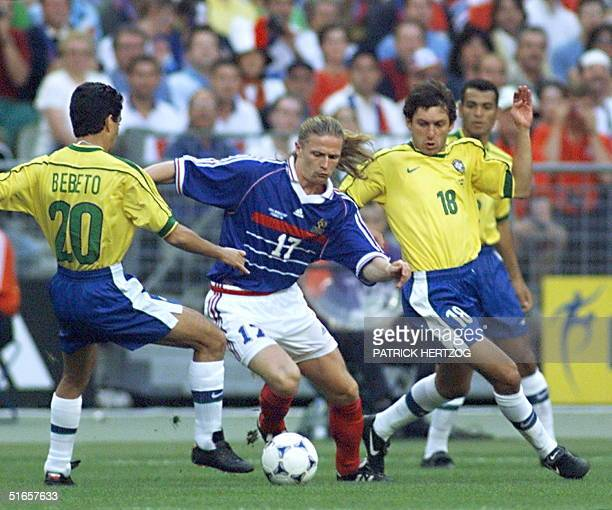 French Emmanuel Petit is challenged by Brazilians Bebeto and Leonardo 12 July at the Stade de France in SaintDenis near Paris during the 1998 Soccer...