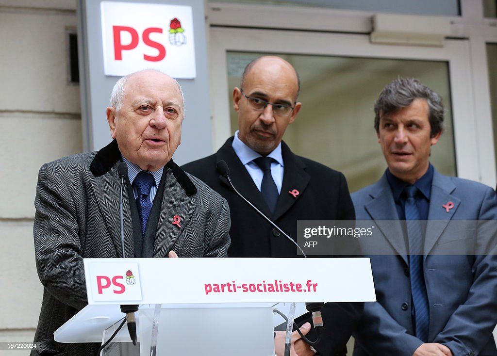 French entrepreneur and co-founder of the Yves Saint Laurent designer house Pierre Berger (L) delivers a speech next to French Socialist Party (PS) First Secretary Harlem Desir (C) and PS spokesman and MP David Assouline (R) as they inaugurate a red ribbon on the facade of the PS headquarters in Paris on November 30, 2012 to mark the upcoming World AIDS Day on December 1.