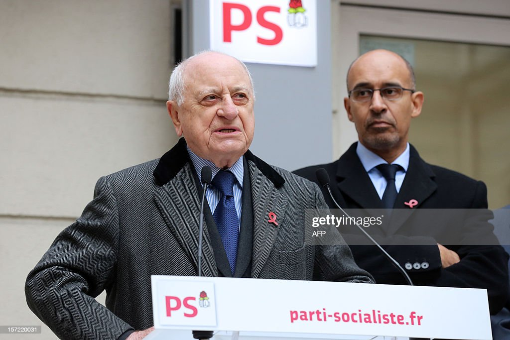 French entrepreneur and co-founder of the Yves Saint Laurent designer house Pierre Berger (L) delivers a speech next to French Socialist Party (PS) First Secretary Harlem Desir as they inaugurate a red ribbon on the facade of the PS headquarters in Paris on November 30, 2012 to mark the upcoming World AIDS Day on December 1.