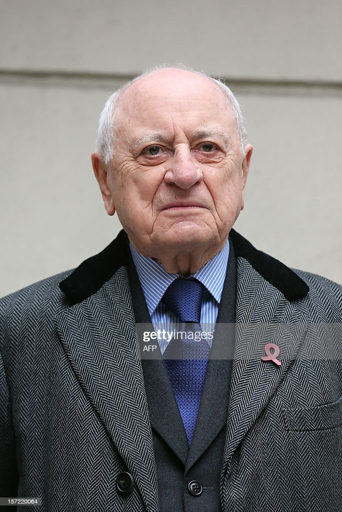 French entrepreneur and co-founder of the Yves Saint Laurent designer house Pierre Berger (L) looks on durin the inauguration of a red ribbon on the facade of the French Socialist Party headquarters in Paris on November 30, 2012 to mark the upcoming World AIDS Day on December 1. AFP PHOTO / THOMAS SAMSON