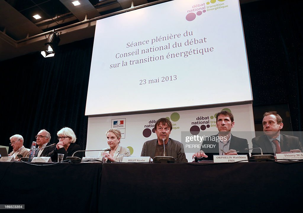 French environmental campaigner Nicolas Hulot (3rd R) speaks alongside the French Minister of the Environment Delphine Batho (4th L) during the start of a meeting by the government committee responsable for the national debate on energy transition and energy sources, in Paris, on May 23, 2013. Nicolas Hulot said that succumbing to the 'temptation' of extracting shale gas and not reducing the proportion of nuclear energy in overall energy output would be 'suicidal'.