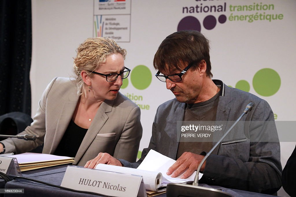 French environmental campaigner Nicolas Hulot (R) speaks with the French Minister of the Environment Delphine Batho during the start of a meeting by the government committee responsable for the national debate on energy transition and energy sources, in Paris, on May 23, 2013. Nicolas Hulot said that succumbing to the 'temptation' of extracting shale gas and not reducing the proportion of nuclear energy in overall energy output would be 'suicidal'. AFP PHOTO / PIERRE VERDY