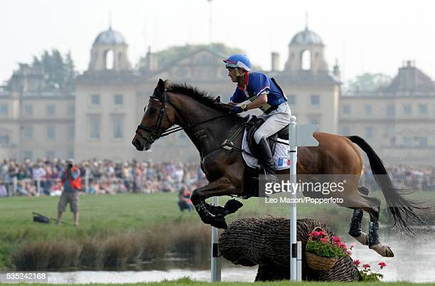 French equestrian Pascal Leroy riding Minos de Petra exits the lake complex with Badminton House in the background during competition in the Cross...