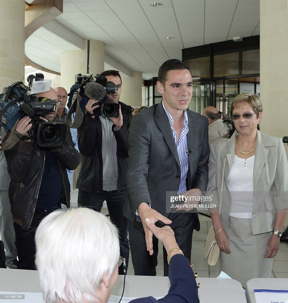 French Etienne Bousquet-Cassagne (C), French far-right Front National (FN) candidate, shakes hand with people as he arrives to vote in Villeneuve-sur-Lot, southwestern France, on June 23, 2013, for the second round ot of a by-election for the National Assembly following the resignation of former Budget minister Jerome Cahuzac. The candidate of the UMP main opposition party took the lead in the first round, closely ahead of Bousquet-Cassagne.