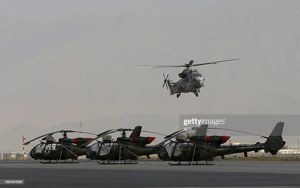 A French Eurocopter Caracal EC 725 helicopter of the 5eme Regiment d'Helicopteres de Combat (5th Combat Helicopter Battalion) flies over parked Viviane Gazelle helicopters, at the French Helicopter Battalion 'Mousquetaire' at the Kabul International airport, in Kabul, on August 18, 2012. France is the fifth largest contributor to NATO's International Security Assistance Force (ISAF), which is due to pull out the vast majority of its 130,000 troops by the end of 2014.