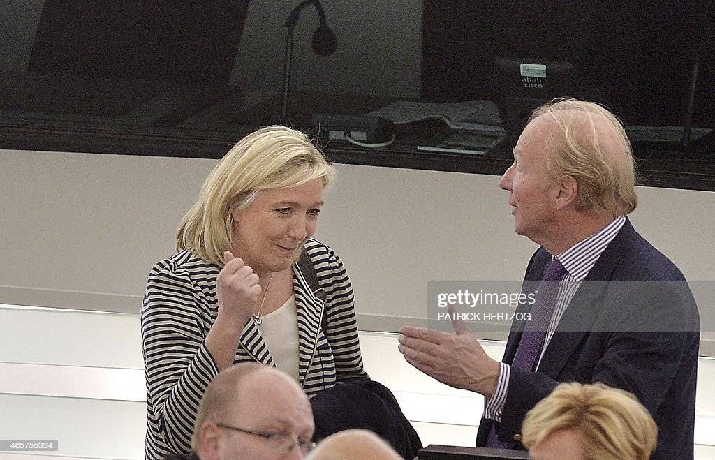 French European Parliament members Marine Le Pen (L) speaks with Brice Hortefeux as they take part in a voting session at the European Parliament in Strasbourg, eastern France, on March 10, 2015. The European Parliament announced Monday that it had alerted anti-fraud investigators to possible financial irregularities committed by France's far-right National Front (FN) party, head by Marine Le Pen, over salaries paid to EU parliamentary assistants.