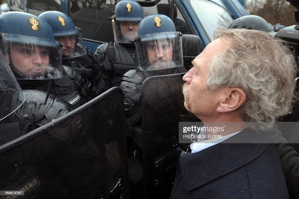 French Europeen deputy Jose Bove stands in front of French anti-riot units of the Gendarmerie on February 6, 2013, during a demonstration of workers from several European Arcelormittal steel plants near the European Parliament in Strasbourg, eastern France. The world's top steel producer ArcelorMittal stumbled into the red last year with a net loss of $3.72 billion (2.75 billion euros) largely due to costs related to Europe.