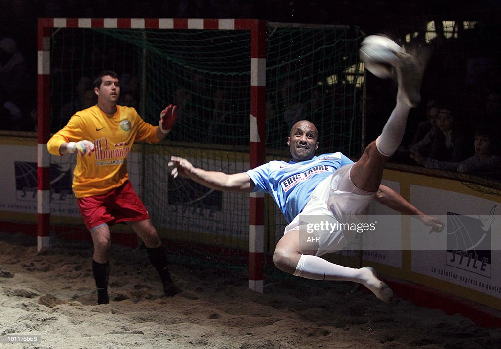 French ex-football player Jean-Pierre Cyprien (R) kicks the ball during the 'Show Beach Soccer, Celebrities' Tournament' on February 9, 2013 in Monaco. The event gathers high-status guests from the worlds of sport and show business in profit for Pascal Olmeta's association 'Un Sourire, Un Espoir pour la Vie' (A Smile, Hope for Life).