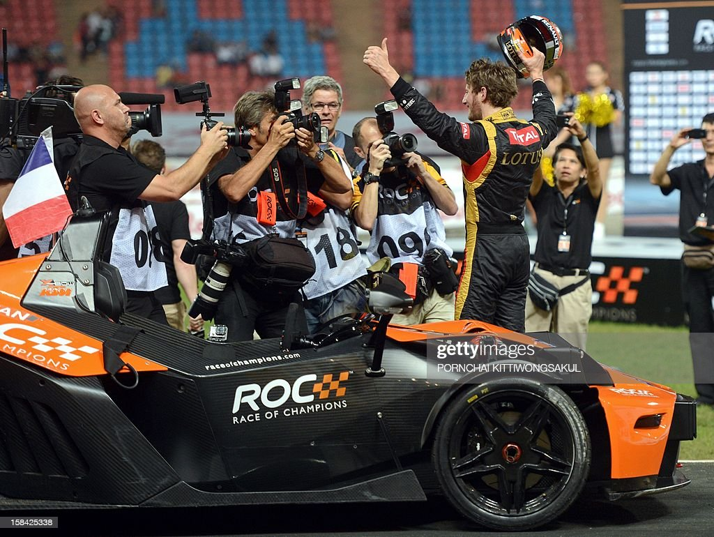 French F1 driver Romain Grosjean (R) celebrates after winning the Race of Champions (ROC) at Rajamangala Stadium in Bangkok on December 16, 2012. The Race of Champions (ROC) brings together heavyweights from all motor racing disciplines in the same type of car.