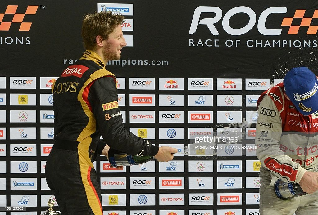 French F1 driver Romain Grosjean (L) celebrates with Champagne after winning the Race of Champions (ROC) next to runner up Danish driver, Tom Kristensen (R) at Rajamangala Stadium in Bangkok on December 16, 2012. The Race of Champions (ROC) brings together heavyweights from all motor racing disciplines in the same type of car.