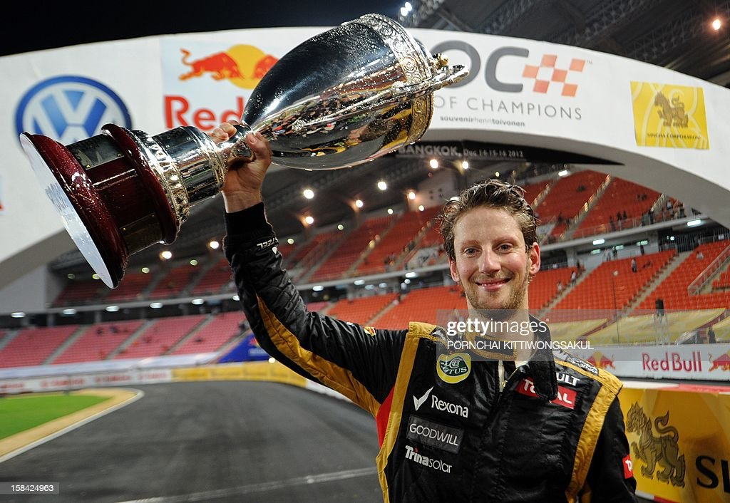 French F1 driver Romain Grosjean celebrates with the trophy after winning the Race of Champions (ROC) at Rajamangala Stadium in Bangkok on December 16, 2012. The Race of Champions (ROC) will take place in Thailand between December 14 and 16 and brings together heavyweights from all motor racing disciplines in the same type of car. AFP PHOTO / PORNCHAI KITTIWONGSAKUL