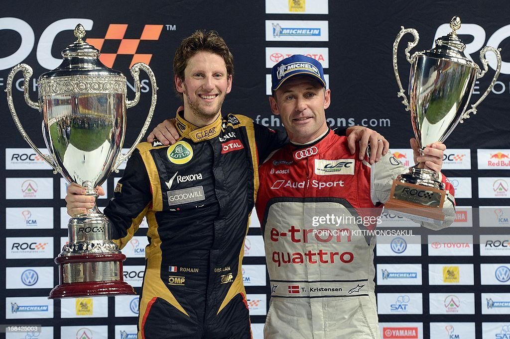 French F1 driver Romain Grosjean (L) poses for photo with trophy after winning the Race of Champions (ROC) next to runner up Danish driver, Tom Kristensen (R) at Rajamangala Stadium in Bangkok on December 16, 2012. The Race of Champions (ROC) will take place in Thailand between December 14 and 16 and brings together heavyweights from all motor racing disciplines in the same type of car.
