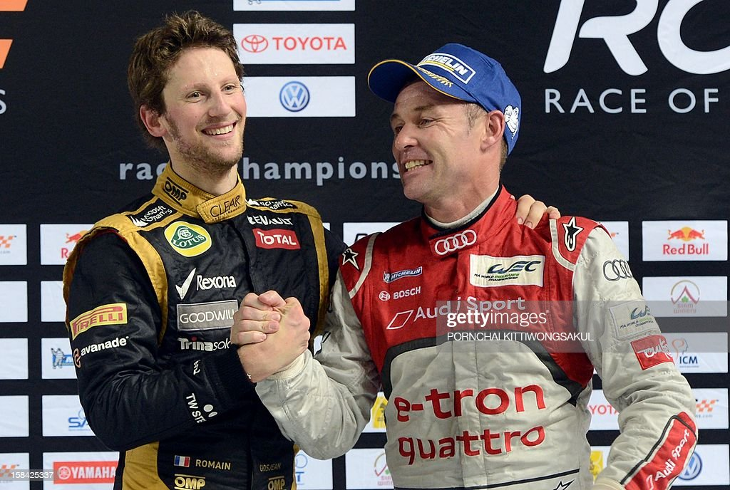 French F1 driver Romain Grosjean (L) shakes hands with Danish driver, Tom Kristensen (R) after winning the Race of Champions (ROC) next to runner up at Rajamangala Stadium in Bangkok on December 16, 2012. The Race of Champions (ROC) brings together heavyweights from all motor racing disciplines in the same type of car. AFP PHOTO / PORNCHAI KITTIWONGSAKUL