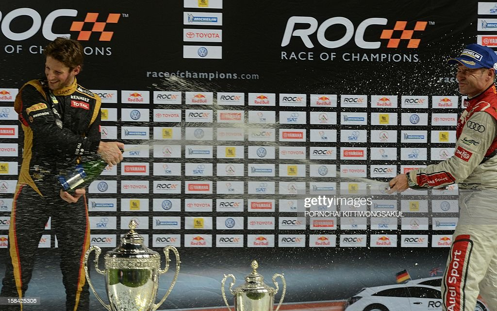 French F1 driver Romain Grosjean (L) sprays champagne after winning the Race of Champions (ROC) next to runner up Danish driver, Tom Kristensen (R) at Rajamangala Stadium in Bangkok on December 16, 2012. The Race of Champions (ROC) brings together heavyweights from all motor racing disciplines in the same type of car.