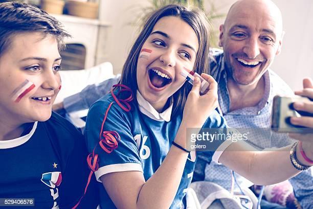 Français famille au football ventilateur tenue prenant une autophoto