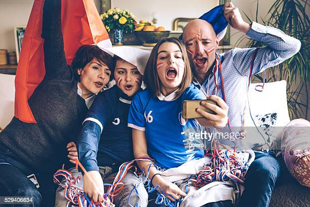 french family soccer fans watching soccer game on smartphone